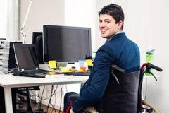 Mann, der im Rollstuhl arbeitet im modernen Büro sitzt Stockbilder