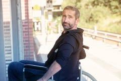 Mann, der im Rollstuhl an der Bahnstation sitzt Lizenzfreie Stockfotos