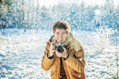 Mann, der im Schnee fotografiert Stockfotografie