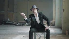 Mann, der im Stuhl in der destoyed Garage mit einem Fedorahut und einem klassischen Anzug und eine Münze leicht schlagen stationi stock footage