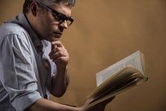 Mann, der im Stuhl- und Lesebuch sitzt lizenzfreies stockbild