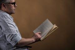 Mann, der im Stuhl- und Lesebuch sitzt lizenzfreie stockbilder