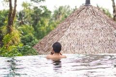 Mann, der im Swimmingpool sich entspannt lizenzfreies stockfoto