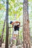 Mann, der im Wald Gymnastik auf Reck tut Lizenzfreie Stockbilder