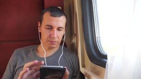 Mann, der im Zug auf die Reiseeisenbahnwagencoupé-Fachreise der Musik hört Zeitlupevideo Mann mit a stock video footage