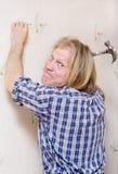 Mann, der innen Nagel zur Wand hammert Stockbild