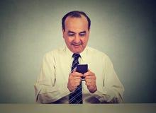 Mann, der am intelligenten Telefon bei Tisch sitzt simst Lizenzfreie Stockfotos