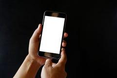 Mann, der intelligentes Telefon auf dunklem Hintergrund hält Lizenzfreie Stockfotografie