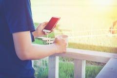 Mann, der intelligentes Telefon verwendet und entspannen Sie sich Zeit Lizenzfreie Stockbilder
