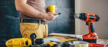 Mann, der intelligentes Telefon verwendet und Tasse Kaffee hält Lizenzfreie Stockfotos