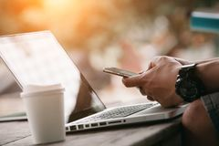 Mann, der Internet auf intelligentem Telefon und Laptop verwendet Stockfoto