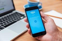 Mann, der iphone 6 darstellende Skype-APP hält Stockfotografie