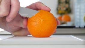 Mann in der Küche, die mit Messer eine Orange in den neuen süßen und gewürzten Scheiben schneidet stock video footage