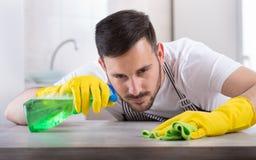 Mann, der Küchentisch abwischt Stockfotografie