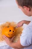 Mann, der Kürbis Jack O'Lantern für Halloween macht Stockfotografie