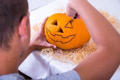 Mann, der Kürbis Jack O'Lantern für Halloween macht Stockfoto
