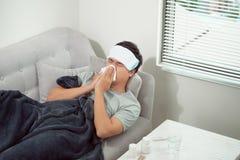 Mann, der kalt sich f?hlt, im Sofa liegt und seine Nase durchbrennt stockfoto