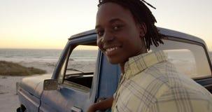 Mann, der Kamera nahe Kleintransporter auf Strand 4k betrachtet stock video footage