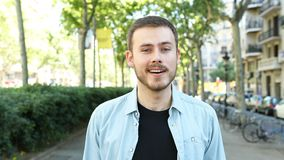 Mann, der Kamera in der Straße betrachtend hört stock video footage