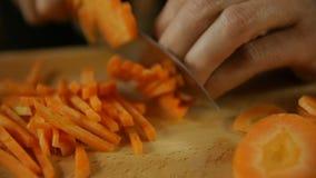 Mann, der Karotte auf hölzernem Brett zerreißt stock video footage