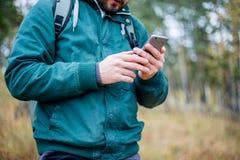 Mann, der Karte am Telefon beim Wandern überprüft stockbild