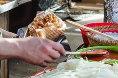 Mann, der Kebab im mittelalterlichen Markt vorbereitet Stockfotografie