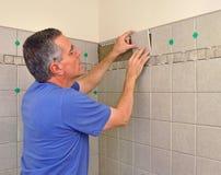 Mann, der Keramikziegel in Badezimmer installiert Stockfotografie