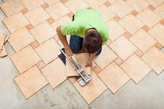 Mann, der keramische Bodenfliesen legt Stockfoto