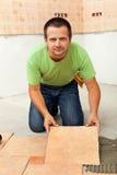 Mann, der keramische Bodenfliesen legt Stockbild