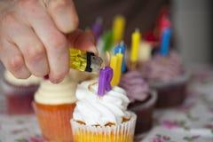 Mann, der Kerzen auf kleinen Kuchen mit Feuerzeug beleuchtet Stockfoto