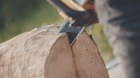 Mann, der Kettensäge verwendet und Holz schneidet stock footage