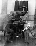 Mann, der Kind hält und Elefanten wäscht (alle dargestellten Personen sind nicht längeres lebendes und kein Zustand existiert Lie Lizenzfreie Stockfotos