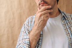 Mann, der Kinn streicht und tiefe Gedanken denkt Lizenzfreie Stockfotos