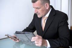 Mann in der Klage bei Tisch mit Telefon und Tablette Lizenzfreie Stockfotografie
