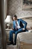 Mann in der Klage, die auf Bett sitzt und das Telefon betrachtet Stockbilder