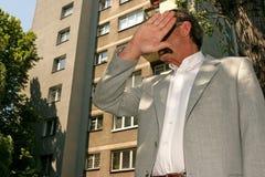 Mann in der Klage, die sein Gesicht versteckt Lizenzfreie Stockbilder