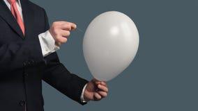 Mann in der Klage lässt einen Ballon mit einer Nadel bersten stockbild