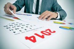 Mann in der Klage mit Diagrammen und einem Kalender 2014 Lizenzfreie Stockbilder