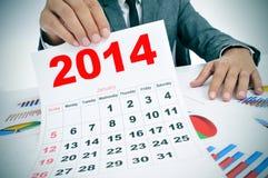 Mann in der Klage mit Diagrammen und einem Kalender 2014 Stockfotografie