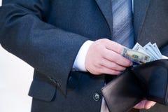 Mann in der Klage mit einem Geldbeutel in den Händen Stockfotografie