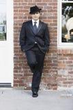 Mann in der Klage und Gleichheit, die an der Wand sich lehnt Lizenzfreie Stockbilder