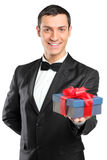 Mann in der Klage und Querbinder, der ein Geschenk gibt Stockbild