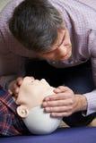 Mann in der Klasse der ersten Hilfe, die Fluglinie auf CPR-Attrappe überprüft Stockfotos