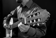 Mann, der klassische Gitarre auf Schwarzweiss spielt stockbild