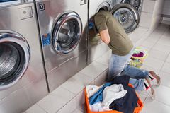 Mann, der Kleidung innerhalb der Waschmaschine sucht Stockbilder