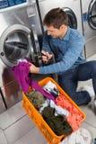 Mann, der Kleidung in Waschmaschine einsetzt stockfotografie