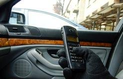 Mann, der Knöpfe des Telefons im Auto betätigt Lizenzfreie Stockbilder