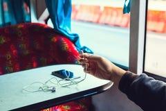 Mann, der Kopfhörer und Handy verwendet stockfoto