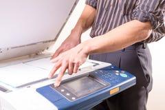 Mann, der Kopierer verwendet, um Kopien von den Dokumenten zu erstellen stockbilder