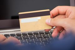 Mann, der Kreditkarte und Laptop verwendet, um online zu kaufen Stockbild